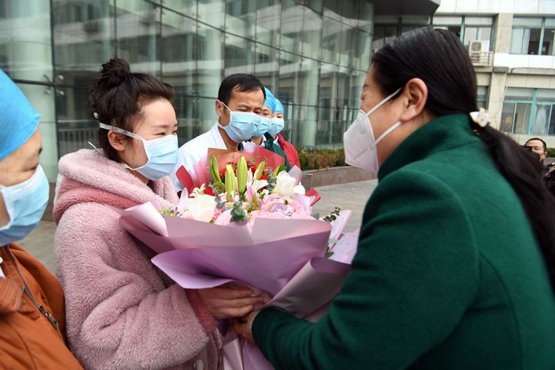 Patient leaves Chinese hospital with flower bouquet and face masks