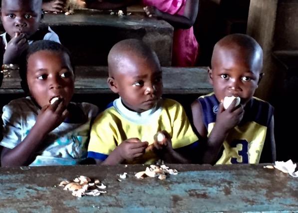 three Malawian children eating eggs