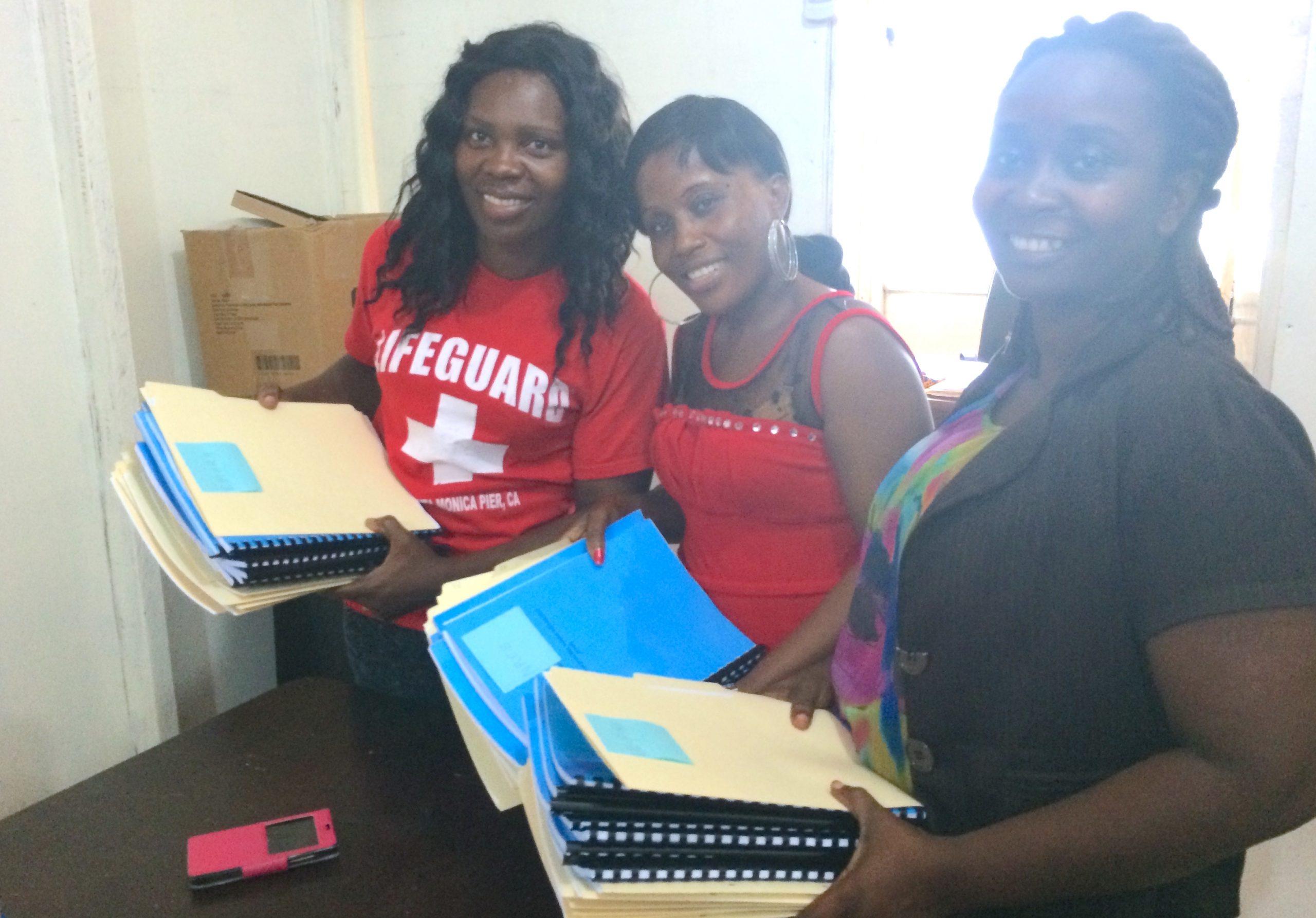 three women holding case files in liberia
