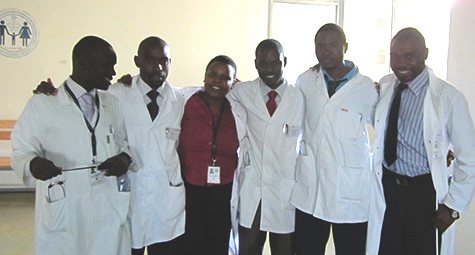 group of six residents inwhite coats with adviser