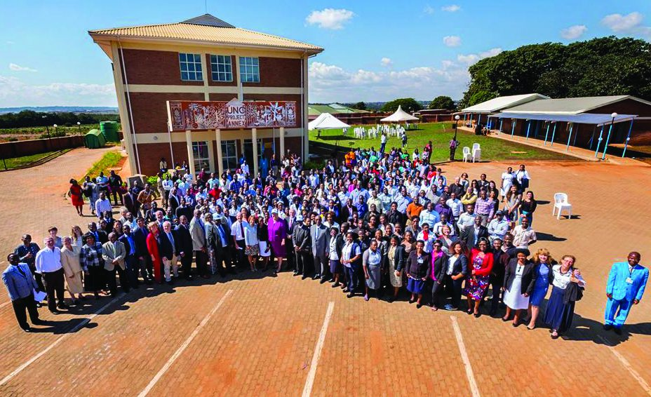 wide-angle group shot of Malawi staff in front of new annex