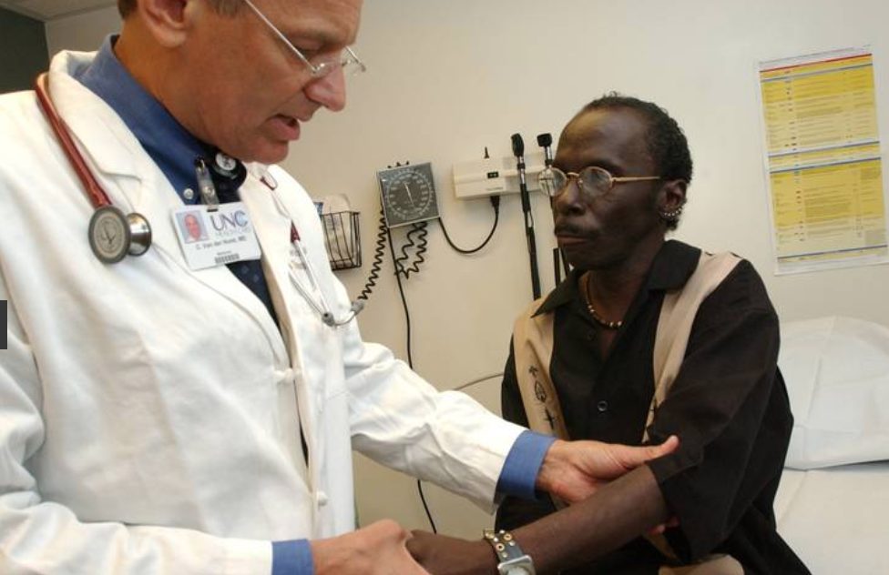 doctor examines patient's arm in clinic