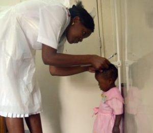 nurse measures girl's height