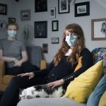 two women with masks at home