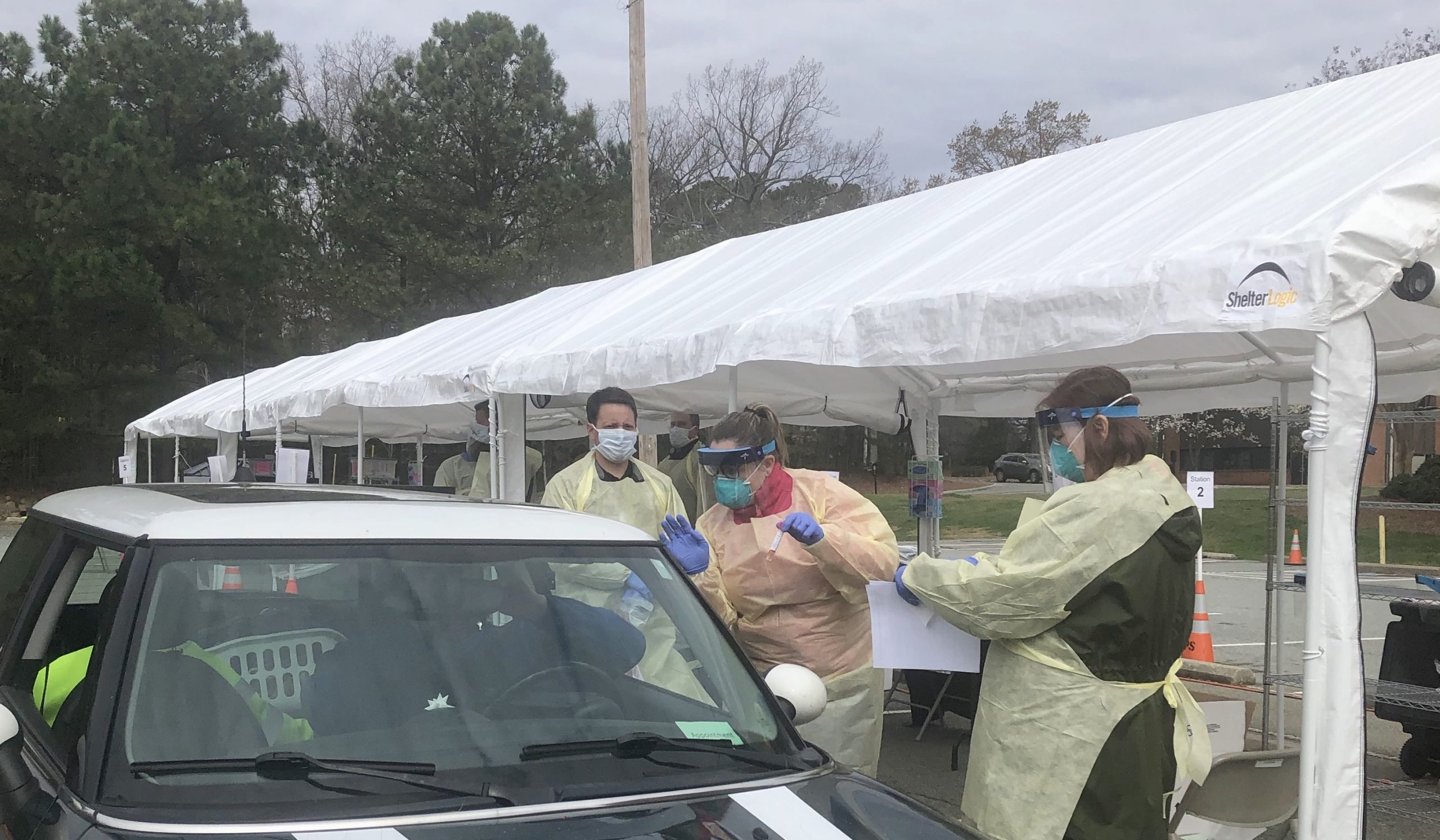 staff in protective equipment take information from person in car